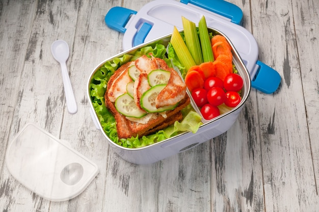 Heated lunch box for carrying and storing food. next to it is a lid and a spoon. in the boxing sandwich and vegetables for a snack. view from above