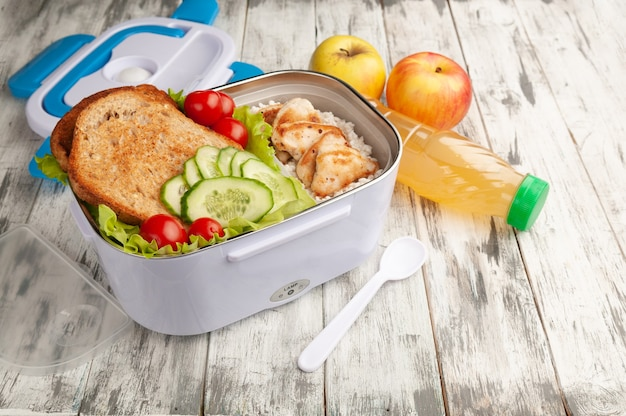 Heated lunch box for carrying and storing food. next to it is a spoon and a lid. the box contains rice with chicken fillet and sandwiches.