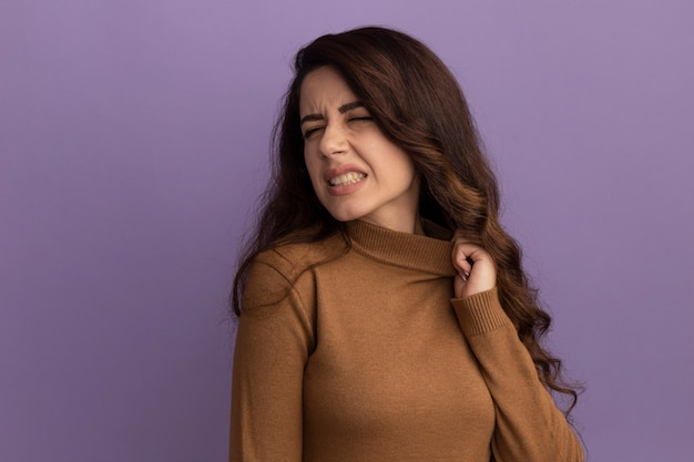Giovane bella ragazza riscaldata che porta il collare della tenuta del maglione dolcevita marrone isolato sulla parete viola