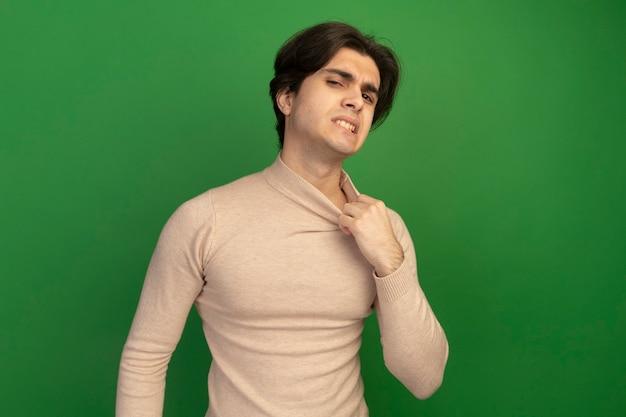 緑の壁に分離された襟を保持している加熱された若いハンサムな男