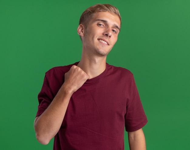 Горячий молодой красивый парень в красной рубашке держит воротник на зеленой стене