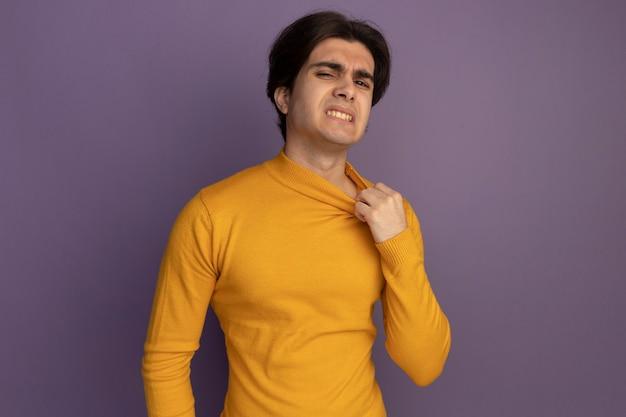 紫色の壁に分離された襟を保持している黄色のタートルネックのセーターを着ている加熱された若いハンサムな男