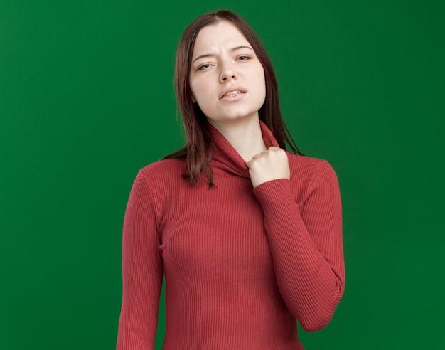 Ragazza graziosa riscaldata che tira il colletto del suo maglione a collo alto
