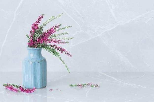 회색 대리석 배경에 파란색 꽃병에 헤더 꽃다발