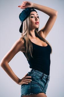 ショートパンツとキャップの若い女性のヘザーグレーの長袖tシャツ、分離、コピースペース、モックアップ。