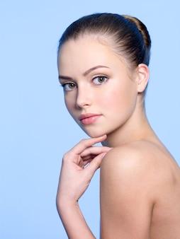 Вересковая чистая кожа молодой красивой женщины на синем