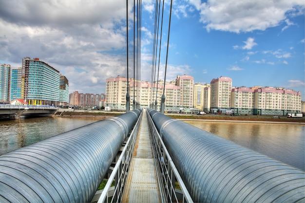 Тепловая магистраль в жилом массиве, стальной трубопровод пересекает реку по вантовому мосту.