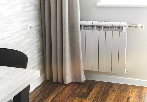 Металлический радиатор отопления, белый радиатор в современном интерьере квартиры с деревянным полом