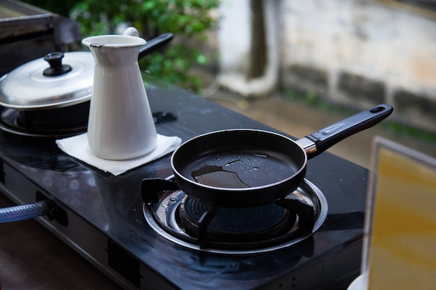 Heating oil in stainless steel pan on gas fueled stove for frying food in outdoor kitchen