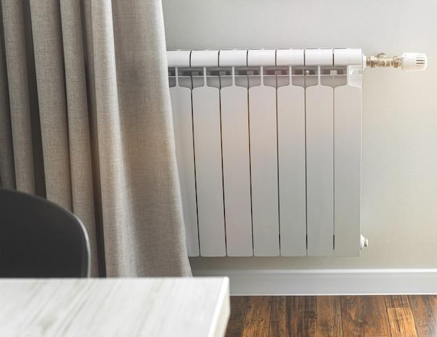 Радиатор отопления в светлом помещении с деревянным ламинатом.