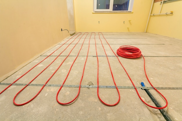 Heating red electrical cable wire installation on cement floor in small new unfinished room with plastered walls. renovation and construction, comfortable warm home concept.
