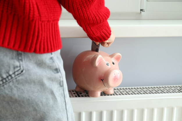 Heating season concept with a girl putting a banknote in a piggy bank.