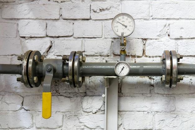 Отрезок трубы системы отопления с манометром, вентилем и фитингами у оштукатуренной кирпичной стены