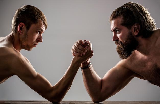 작은 약한 남자를 레슬링하는 무거운 근육이 수염 남자 팔