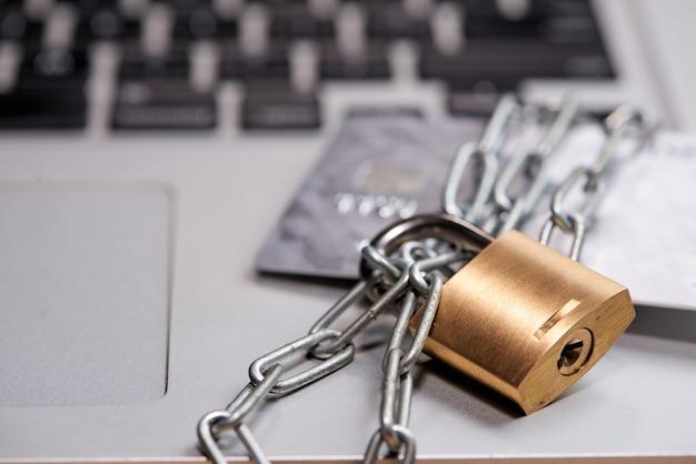 노트북 주위에 자물쇠가 달린 무거운 사슬과 탁자 위에 신용 카드.