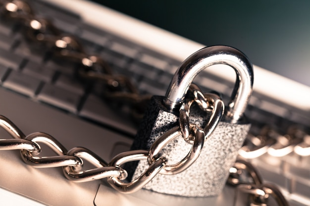 Heavy chain with a padlock around a laptop, close up