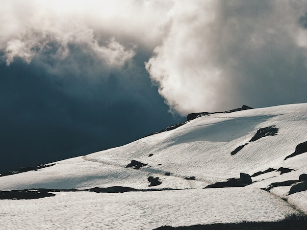 Heavy clouds hang over the mountains covered with snow