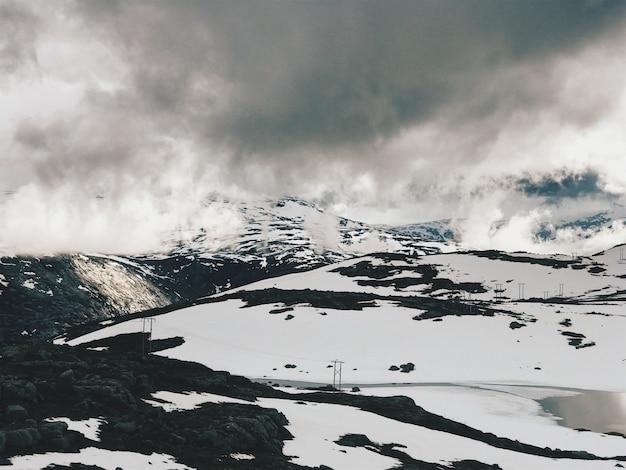 Тяжелые облака висят над горами, покрытыми снегом