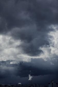 重い暗い雲が建物を覆っています。雲の下に大気汚染があります。