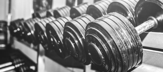 ジムで生で横たわっている重いダンベル。フィットネススポーツの動機。幸せな健康的なライフスタイルの生活。バーウェイトを使用したエクササイズ。黒と白の写真。