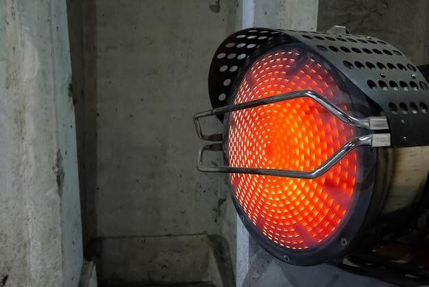 Сверхмощный промышленный обогреватель, выдувающий горячий воздух в холодных интерьерах здания. пропеллер теплового компрессора или тепловентилятора, нагнетающий теплый воздух в холодные конструкции.