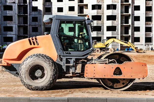 Мощный вибрационный каток для укладки асфальта. дорожное строительство. строительство дорог и городских транспортных коммуникаций. тяжелая техника.