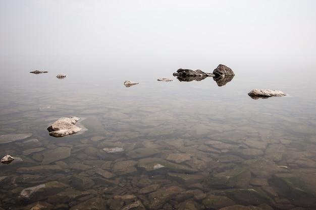 石と澄んだ水で湖の上の濃い霧