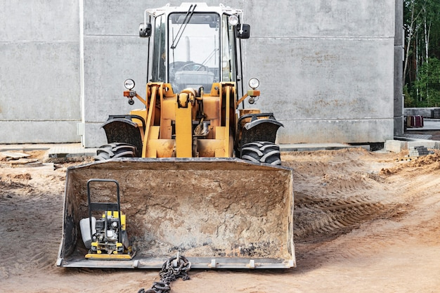 Heavy front loader on a construction site with a construction tool in the bucket. equipment for earthworks, transportation and loading of bulk materials - earth, sand, crushed stone.