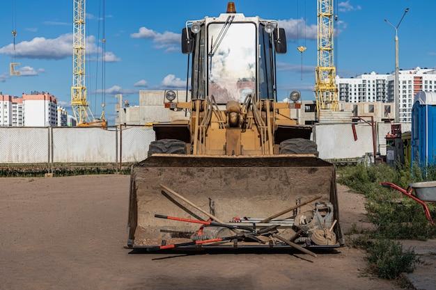 Тяжелый фронтальный погрузчик на строительной площадке со строительным инструментом в ковше. оборудование для земляных работ, транспортировки и погрузки сыпучих материалов - земли, песка, щебня.