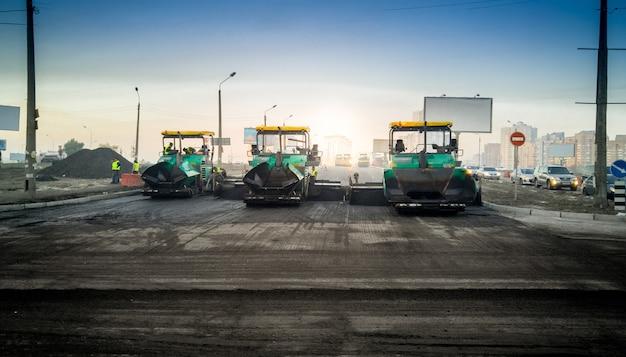 新しい道路にアスファルトを敷設する重工業機械