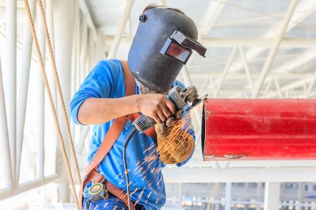 Heavy industrial worker grinding steel pipe by electric wheel grinding