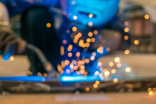 Работник тяжелой промышленности сварщик в защитной маске рука дуговой сварки факел, работающий на металлической конструкции