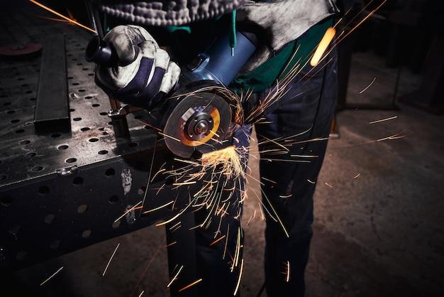 Рабочий тяжелой промышленности режет сталь на угловой шлифовальной машине.
