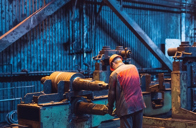 Heavy industry worker working hard on machine. rough industrial environment.