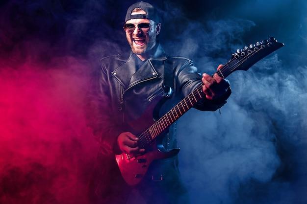 ヘビーメタルのミュージシャンはエレキギターを弾いています。スタジオで撮影します。