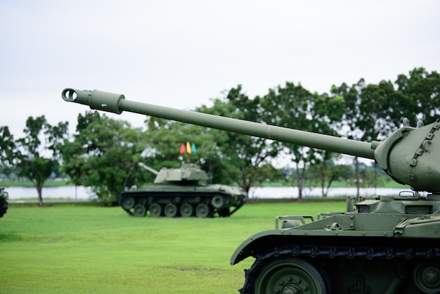 Тяжелый военный танк припаркован на траве