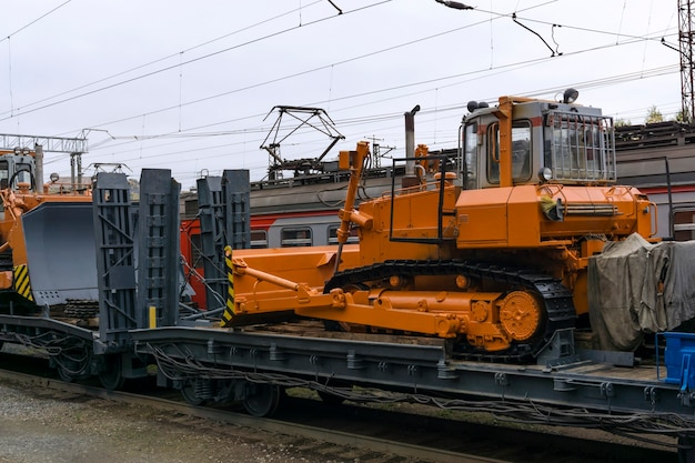 Heavy orange bulldozer stands on the flatcar of the train for accident recovery work