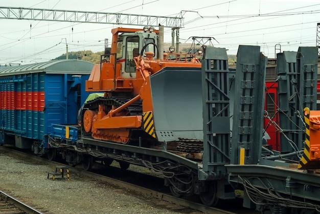 重いオレンジ色のブルドーザーが事故復旧作業のために列車の長物車の上に立っています