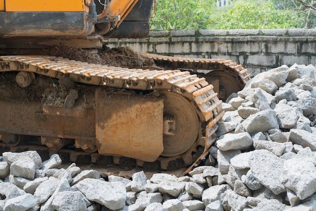岩が付いている丘の上に立っているシャベルと重い有機掘削機