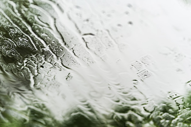 Heavy rain background, raindrops on window glass outdoors