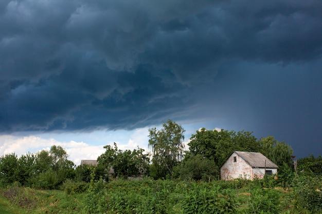 遠くの村の廃屋近くで大雨。緑の自然