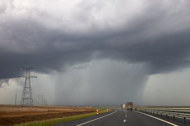 Heavy rain pours from a cloud hanging over the highway