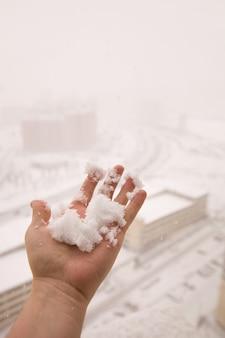 大雪と街の高さからの眺めと男性の手が新たに降った雪玉を握る