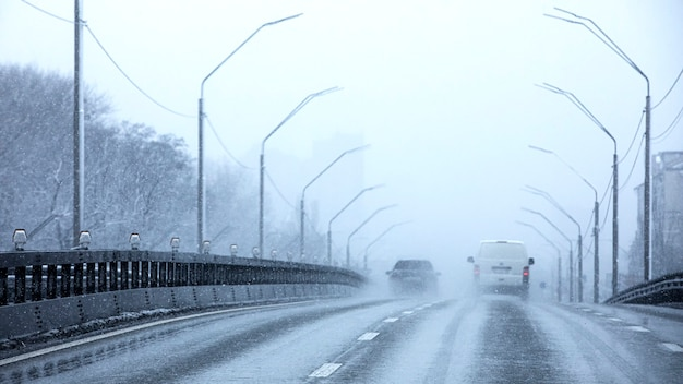 Heavy snowfall and poor visibility on the road.