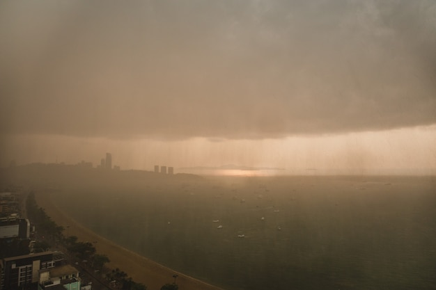 Тяжелые штормовые дождевые облака над современным городом на берегу моря