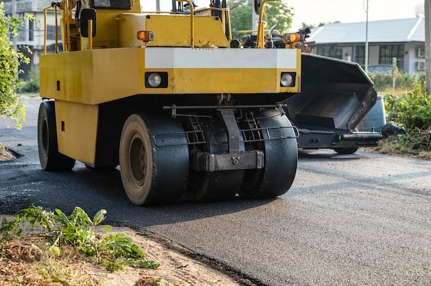 Желтый паровой каток с тяжелой вибрацией или уплотнитель грунта, работающий на дороге с асфальтовым покрытием на строительной площадке