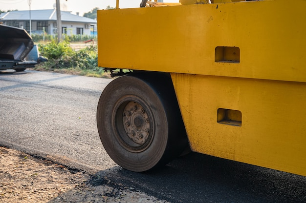 Heavy vibration yellow steamroller or soil compactor working on hot-mix asphalt pavement road at construction site