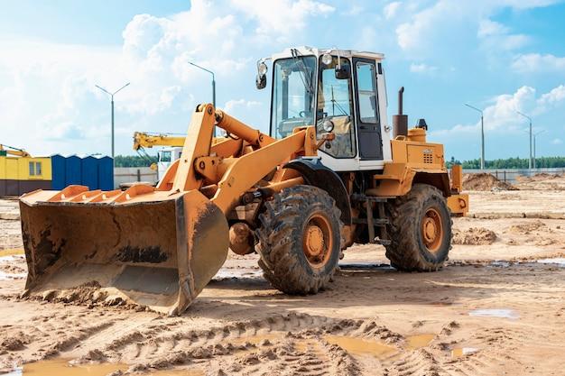Тяжелый колесный погрузчик с ковшом на стройке. оборудование для земляных работ, транспортировки и погрузки сыпучих материалов - земли, песка, щебня.