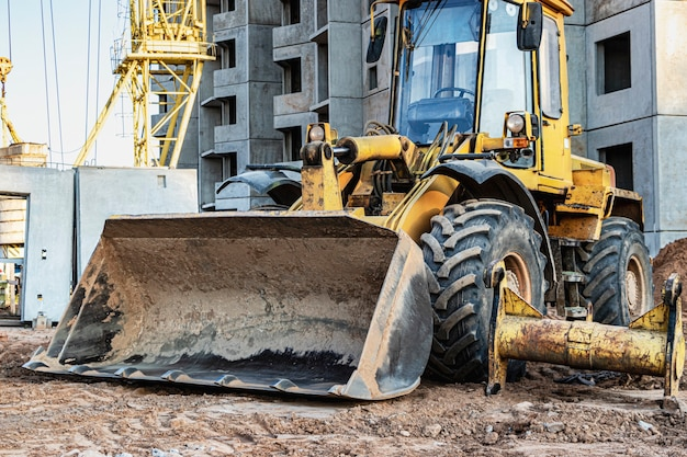 Heavy wheel loader with a bucket at a construction site. equipment for earthworks, transportation and loading of bulk materials - earth, sand, crushed stone.
