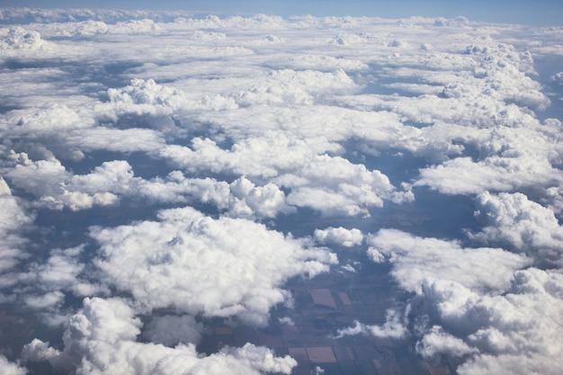 青い空と太陽の光で、飛行機のビューからの重い白/灰色の雲、飛行機は雲の上を飛んでいます